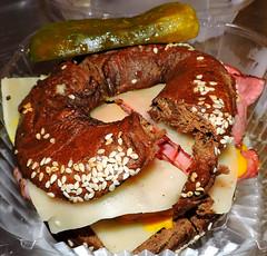Rueben sandwich on a sesame pumpernickel bagel; kosher dill pickle (Will S.) Tags: mypics ottawa ontario canada bagel reubensandwich montrealsmokedmeat cheese sauerkraut kosherdillpickle swisscheese swiss smokedmeat beef mustard honeymustard