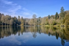 Stourhead - Looking Across the Lake. (margaretgeatches) Tags: stourhead wiltshire nationaltrustproperty ripples reflections clouds blue skies trees lake winter