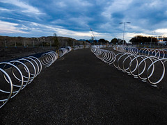 The Bike Park (Steve Taylor (Photography)) Tags: spiral bikerack park fence lamppost crane silver blue metal chrome gravel newzealand nz southisland canterbury christchurch northnewbrighton curve shiny bicycle bike cycle sky cloud