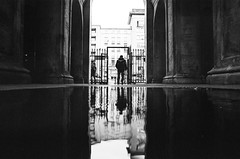Pillars (ewitsoe) Tags: warsaw blackandwhite bnw monochrome analogue analog film rolleirpx400 nikonfm2 street reflection grain water puddle entrance man silhouettebuildings 28mm urban life travel