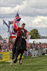 Last to Leave (meniscuslens) Tags: bucks county show buckinghamshire aylesbury weedon flag soldier horse household cavalry grass arena event crowd sky clouds