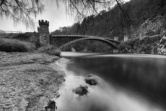 """fine art long exposure of the famous Craigellachie Bridge arching across the River Spey near Aberlour, Moray, Scotland (grumpybaldprof) Tags: """"craigellachiebridge"""" craigellachie """"castironarchbridge"""" bridge iron """"riverspey"""" aberlour """"thomastelford"""" 1814 """"46mspan"""" river water crossing """"listedstatus"""" moray scotland bw blackwhite """"blackwhite"""" """"blackandwhite"""" noireetblanc monochrome """"fineart"""" ethereal striking artistic interpretation impressionist stylistic style contrast shadow bright dark black white illuminated mood moody atmosphere atmospheric calm peaceful tranquil restful """"wideangle"""" ultrawide """"longexposure"""" """"neutraldensity"""" nd canon 7d """"canon7d"""" sigma 1020 1020mm f456 """"sigma1020mmf456dchsm"""""""