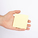 Hand holding empty yellow paper isolated on white background