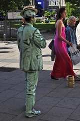 Mime with Two Hats (AntyDiluvian) Tags: gothenburg sweden pedestrianzone street mime man greensuit skimmer boater strawhat girl woman reddress