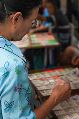 A woman in blue shirt is deciding to buy lottery for luck - Bangkok. (baddoguy) Tags: 7079 years active seniors adult adults only bangkok blue buying chance closeup clothing color image copy space decisions focus on foreground hand holiday event hope concept human body part individuality kiosk lottery luck market stall one person senior woman women opportunity own goal people photography ratchaprasong shopping side view standing thailand vertical wealth wellbeing