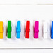 Small, multicolored cloth hangers on the white wooden background