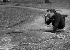 Photographer as model (kristenscotti) Tags: olympus chicago chicagoland evanston usa blackandwhite bw black white streetphotography street spring winter bokeh capturestreets visuals microfourthirds 50mm portrait outside art city people monochrome penf mono exterior day park man photographer absoluteblackandwhite camera leaves trees trail nature scenic checkers chess brick