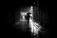Strangers in the night (Paul Wrights Reserved) Tags: shadow shadows lightandshadow higlight vanishingpoint leadinglines tunnel streetphotography streetlights street london londonstreets pinhole light darkness walking rain raining umbrella
