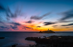 Godrevy Afterglow (Vigor11) Tags: ower island beacon evening sunset ocean light glow sea stacks lines lighthouse rocks longexposure seascape sun solitary alone tall large cliff incomingtide reflection shadow horizon still peaceful calm sky orange yellow magenta red blue brown white colourful warm water noclouds gold goldenarchitecture building landscape