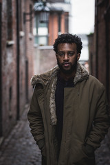 Alrasheed 1 (Qais Nidhal) Tags: portrait person alley brickwall face faded shallow united kingdom uk coventry street pathway old buildings lamp walk walking sudan africa black dark skin cold winter coat afro curly serious hope canon 50mm 600d 14