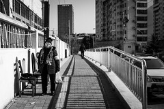 Waiting room (Go-tea 郭天) Tags: qingdao shandong républiquepopulairedechine cn sidewalk pavement lines chairs sun sunny shadow cold winter old woman lady wrinkles waiting wait scarf hat bag plastic alone lonely pedestrian street urban city outside outdoor people candid bw bnw black white blackwhite blackandwhite monochrome naturallight natural light asia asian china chinese canon eos 100d 24mm prime portrait
