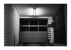 Garage Illuminated (Thomas Listl) Tags: thomaslistl blackandwhite biancoenegro noiretblanc monochrome film filmphotography analog minoltax700 minolta kodak tmax tmax400 pushingfilm push1stop light lamp topography mundane vintage mood atmosphere dark