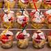 Obstsalat to go mit Erdbeeren, Melone und Kokosnuss im Plastikbecher mit Plastikgabel in der Markthalle La Boqueria in Barcelona, Spanien