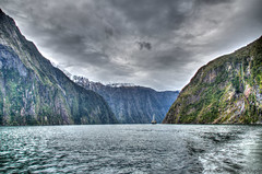 The Voyage (myshutterworld) Tags: newzealand south island landscape mountains peaks serene picturesque gorgeous southland milfordsound hdr spectacular beautiful mind blowing amazing middle earth heavenonearth lake fiordlandnationalpark cloudy dark blue green water nature sky grass trees rocks fiord boat waves greatphotographers