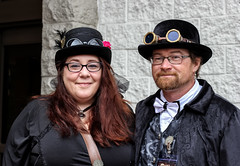 Steampunk Couple (J Wells S) Tags: steampunkcouple portrait candidportrait beard costumes smile dressup tophat goggles bowlerhat bowtie feathers steampunksymposium hat eastgate cincinnati ohio cosplay holidayinneastgate