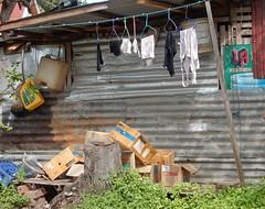 Boxes and Laundry (mikecogh) Tags: luangprabang washing hanging junk corrugatediron boxes pile clothes