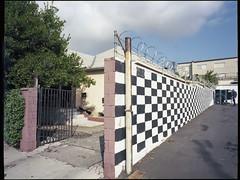 Cinderblock study -- the wall next door. (ADMurr) Tags: la hollywood checkerboard wall cinderblock razor wire checkered flag hasselblad swc 38mm zeiss kodak 645 dab8832edit ektar 120 film