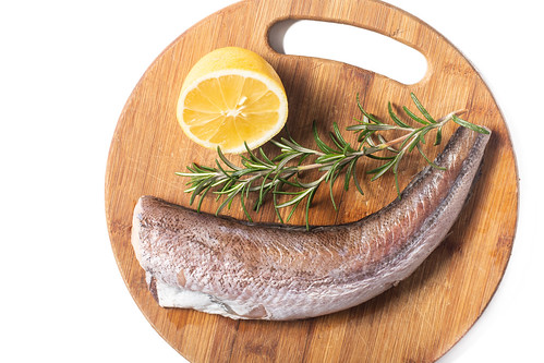 Hake Fish with Rosemary and Lemon on the wooden board