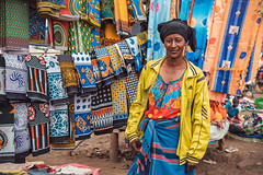 Any Color You Like.. (u c c r o w) Tags: colors colorful woman tanzania africa arusha bazaar shawl scarf yellow red blue street streetlife urban urbanlife city citylife tanzanian texture portrait vendor seller