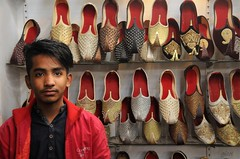 in someone else's shoes (gicol) Tags: shoes shop scarpe zapatos negozio tienda commesso owner seller boy ragazzo kid man young giovane joven chico dark scuro occhi eye ojos hair capelli pelo faisalabad clocktower pakistan punjab downtown centro