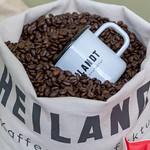 Weiße Kaffeetasse liegt in Sack voller gerösteter Kaffeebohnen thumbnail