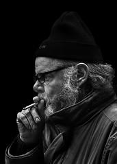 Portrait (D80_527084) (Itzick) Tags: denmark copenhagen bw blackbackground bwportrait beard man cigarette streetphotography smoking glasess hat portrait d800 itzick