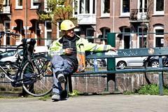 Man At Work - Kwakersstraat Amsterdam (FaceMePLS) Tags: amsterdam nederland thenetherlands facemepls nikond5500 straatfotografie streetphotography werkman arbeider bouwvakker constructionworker helmet helm handy gsm mobieletelefoon smartphone uniform bank bench bouwhelm spa