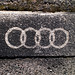 AUDI sign sprayed with black paint on the street