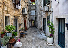An Alley in Dubrovnik (Jocelyn777) Tags: streets alley laundry houses buildings achitecture stone stonehouses towns oldtowns starigrad dubronik croatia balkans travel plantsandflowers flowerpots chairs