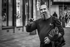 A Source Of Ignition (Leanne Boulton) Tags: portrait urban street candid portraiture streetphotography candidstreetphotography candidportrait streetportrait eyecontact candideyecontact streetlife man male face eyes beard expression mood feeling emotion hand waving gesture smoke smoker smoking cigarette tone texture detail depthoffield bokeh naturallight outdoor light shade city scene human life living humanity society culture lifestyle people canon canon5dmkiii 70mm ef2470mmf28liiusm black white blackwhite bw mono blackandwhite monochrome glasgow scotland uk