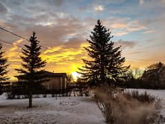 Morning colours 2 (darletts56) Tags: sky blue cloud clouds grey yellow orange white sun ray tree trees snow green winter home homes house houses yard yards sunrise morning wire line lines wires bush bushes village saskatchewan canada prairie exhaust road country vehicle