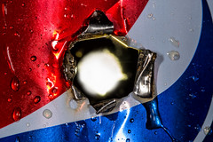 Tin Can Alley (Mark Wasteney) Tags: macromondays holes can hole redwhiteblue pepsi backlighting backlit lessthanthreeinches closeup shot punctured damaged