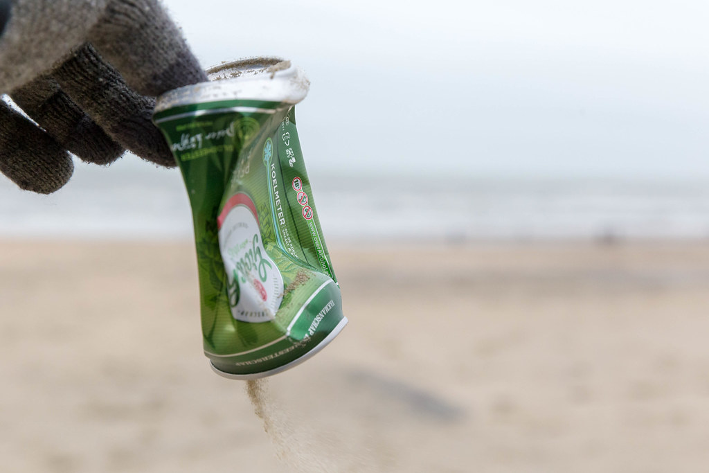 Hand picks up old beer can from the beach and reduces pollution