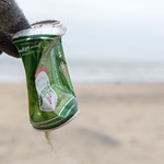 Hand picks up old beer can from the beach and reduces pollution thumbnail