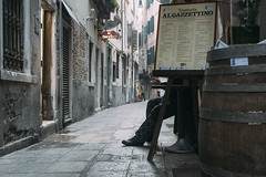 al gazzettino (markfly1) Tags: italy venice 2019 candid photo street photography streetphoto cobbled pavement unusual pose funny scene menu cafe restaurant man sitting outside hidden obscuered nikon d750 35mm manual focus lens