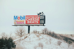 Spotted Cow with cheese and brats. (Cragin Spring) Tags: unitedstates usa unitedstatesofamerica midwest wisconsin wi rural snow sign billboard spottedcow hill cheese brats dunkindonuts mobil