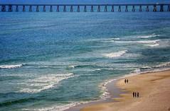 beach walkers (Bluescruiser1949) Tags: beach bridge shore lowtide waves ocean oceanwaves warm water sand people