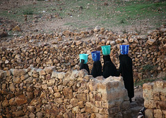 Women In Black Walking In Line With A Bucket On Their Head To Go Fetch Water, Shahara, Yemen (Eric Lafforgue) Tags: adult arabia arabiafelix arabianpeninsula architectural architecture bodymovement bucket burka colourpicture container dailylife day female fulllength group historical history horizontal lowwall muret placeofinterest realpeople recipient shahara shaharah silhouette togetherness veiledwoman waterduty waterresource watershortage woman yemen 0004yemenlafforgue