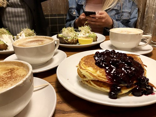 A Breakfast Table with Blueberry Pancakes and Avocado Toasts
