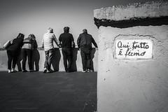 """Qui tutto è fermo"" (Laura Sergiampietri) Tags: bn people bw biancoenero blackwhite tarquinia italy lazio vincenzocardarelli poetry wall men women belvedere viewpoint smcpentaxda1770mmf4alifsdm smcpda1770mmf4alifsdm watching watchers still urban"