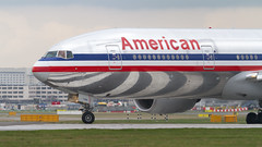 American Reflections. (spencer_wilmot) Tags: aa american heathrow boeing777 triple7 tripleseven americanairlines reflections runway heavy twin cheatline egll lhr lhregll departure aircraft plane airplane passengerplane passengerjet jetliner airliner jet