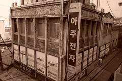 """Seoul Korea Seun Electronics Market 2019 view from the upper-deck - """"Gritty City"""" (moreska) Tags: seoul korea seun electronics market 2019 gritty faded decaying urban structure architecture blackandwhite sepia monochrome hangul sign english signage corrugated rooftops wires 1970s oldschool brickwork momandpop wholesale shopping travel tourism rok asia"""