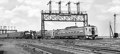 New Haven Railroad departing RDC train led by Budd RDC-1 # 20, along with a departing New York Central RS-3 # 8351, that is seen while leading a commuter train near signal bridge # 9, at Boston, Massachusetts, ca late 1950's (alcomike43) Tags: newhavenrailroad newyorknewhavenhartfordrailroadcompany bostonmassachusetts southstation station depot railroads trains budd passengertrains commutertrains localtrains rdctrains rdc1 20 signalbridge9 tracks rails ties ballast rightofway roadbed mainline jointedsectionrail tieplates spikes anglebars switch turnout signallantern bladesemaphoresignals blocksignals railroadfacility photo photograph bw blackandwhite old vintage historic classic newyorkcentral passenger bostonalbany cars coach heavyweightpassengercars passengercars alco rs3 8351 diesels engines locomotives dieselengine diesellocomotive dieselelectriclocomotive