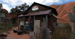 Canteen (motobazzi) Tags: secondlife sl virtual sim region mesh bar ravern pub barroom saloon taproom cantina canteen wateringhole landscape portrait pic picture photo signs antique rural southwest junk flag beer shack cactus americana trees clouds sky shadows sand rock cigarette memorabilia historic traditional dusty antiquated dated aged patina eclectic