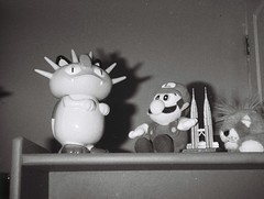 Meowth and Luigi (Matthew Paul Argall) Tags: hanimex110if fixedfocus 110 110film subminiaturefilm lomographyfilm blackandwhite blackandwhitefilm 100isofilm meowth luigi gaming videogames bedroom