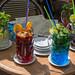 Vier bunte Cocktails in Biergläsern mit Limonenstücke, Orangenscheiben Minzblätter und Strohhalme im La Terraza Club in Barcelona, Spanien