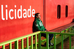 'At the center of it all ... ' (Canadapt) Tags: tróia portugal boat ferry man street red green fence colour canadapt