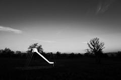 On the playground (stefankamert) Tags: playground slide sky noir blackandwhite blackwhite noiretblanc trees clouds grain ricoh gr ricohgr grii light landscape sun reflections