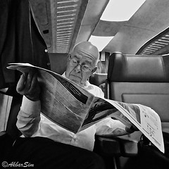 TRAVELLING BY TRAIN (Akbar Simonse) Tags: holland netherlands nederland people candid trein train reiziger passagier krant krantenlezer pater newspaper zwartwit bw bn blancoynegro blackandwhite vierkant square akbarsimonse streetphotography straatfotografie streetshot straatfoto publictransport glasses bril spectacles 1eklas firstclass reading