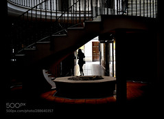 Darkness at Noon (HoustonHVAC170) Tags: ceiling staircase balcony illuminated column window light spiral silhouette candid street photography urban dark stairs black city white old shade sunlight door lights colors beautiful girl dramatic building contrast fine art steps textures perspective woman two people